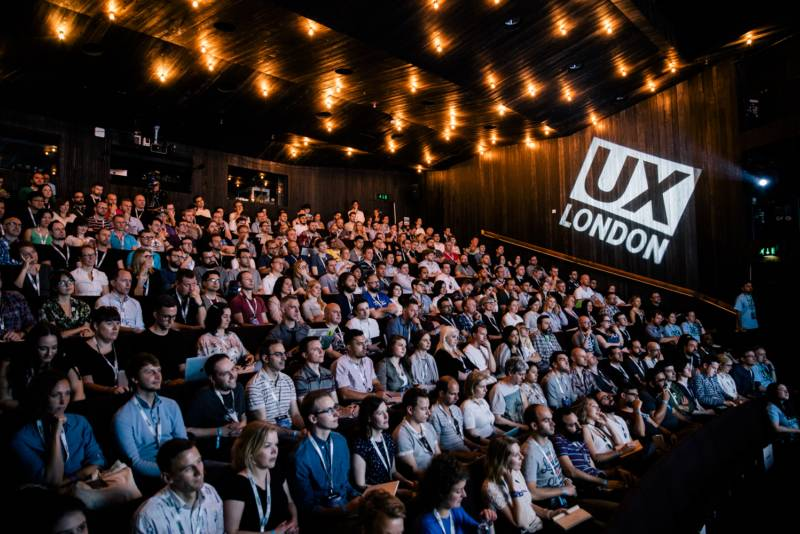 An ambiently lit view over the UX London conference hall. A UX London logo is projected on the wall.